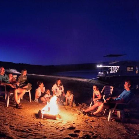 Family enjoying fire on Lake Powell beach